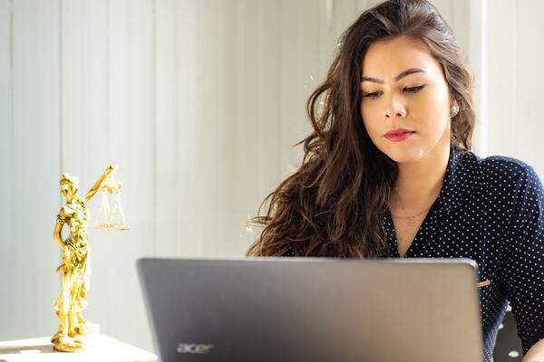 A imagem contém uma advogada olhando para a tela do seu notebook. Ao seu lado há uma estatueta do símbolo da justiça.