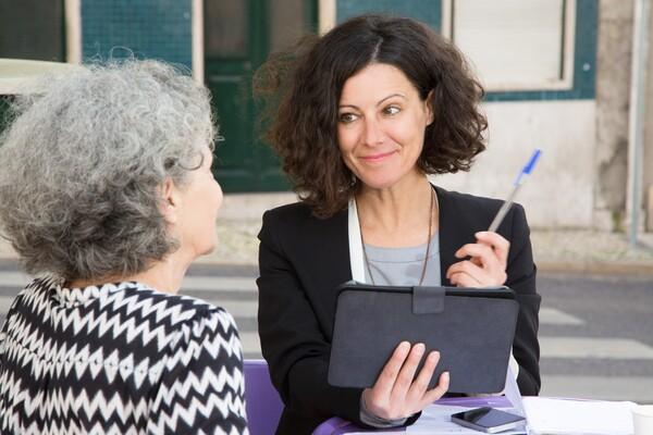 A imagem contém uma advogada previdenciária fazendo o atendimento de uma senhora. A advogada soube como iniciar na advocacia previdenciária e hoje atua com excelência.